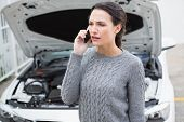 pic of annoying  - Annoyed woman on the phone beside her broken down car in a car park - JPG