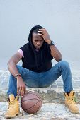 picture of swagger  - Portrait of a young african american man sitting on sidewalk with basketball - JPG
