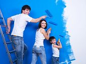 stock photo of wall painting  - Happy young family with little son painting the wall - JPG