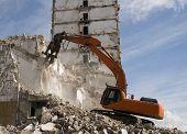 foto of crusher  - Hydraulic orange crusher excavator demolishing old building - JPG