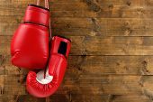 stock photo of boxing  - Pair of boxing gloves on wooden planks background - JPG