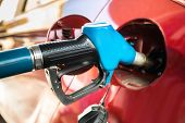 stock photo of fuel economy  - Red Car At Gas Station Being Filled With Fuel