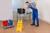 image of janitor  - Male Janitor Suffering From Back Pain While Mopping In Office - JPG