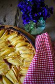 image of helleborus  - French apple tart on the old rustic table with flowers and napkin - JPG