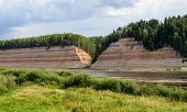 stock photo of ravines  - Geological outcrop with deep ravine on the Sukhona River near the former village Opoki North Russia - JPG