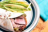 stock photo of flank steak  - flank steak burrito on home made flatbread with garlic fried string beans - JPG
