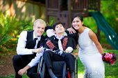 stock photo of biracial  - Biracial bride and groom with her little disabled brother in wheelchair on their wedding day - JPG