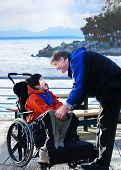 image of biracial  - Handsome father talking with disabled biracial son outdoors by lake - JPG