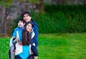 stock photo of biracial  - Disabled biracial child riding piggy back on his sister family surrounding him together at park. ** Note: Soft Focus at 100%, best at smaller sizes - JPG