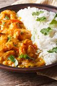 image of cilantro  - Shrimps in curry sauce with rice and cilantro closeup on a plate - JPG