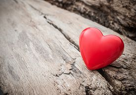 stock photo of love hurts  - Red heart in crack of wooden plank - JPG