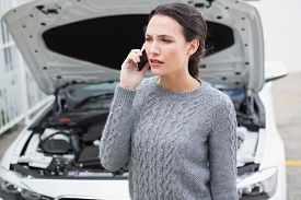picture of annoying  - Annoyed woman on the phone beside her broken down car in a car park - JPG