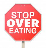 pic of reduce  - Stop Over Eating words on a red road sign as warning to reduce food intake - JPG