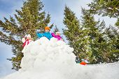 stock photo of snowball-fight  - Children playing snowball fight game together standing behind the snow wall with fir forest on the background during winter day - JPG