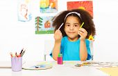 picture of rod  - Small African girl holding cuisenaire rods learn to count while sitting at the table and wall behind with children drawings - JPG