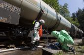 stock photo of decontamination  - A team working with toxic acids and chemicals is securing a chemical cargo train tanks crashed near Sofia Bulgaria - JPG