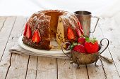 foto of icing  - Rustic style bundt cake decorated with strawberries and sprinkled with icing sugar - JPG
