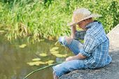 stock photo of chums  - Teenager angler is looking down at water from concrete bridge - JPG