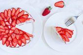 picture of strawberry  - Sliced piece of gourmet homemade celebration strawberry cake sweet dessert food with whipped cream and fresh strawberries on white kitchen table background - JPG