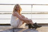 stock photo of woman boots  - Portrait of a blond woman wearing white lace dress and short black boots with lake behind her enjoying sun - JPG
