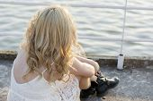 pic of woman boots  - Back of a blond woman wearing white lace dress and short black boots looking to the lake enjoying sun. Fashion for young people.