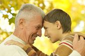 stock photo of grandfather  - Grandfather and grandson together in autumn park - JPG