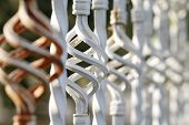 stock photo of wrought iron  - Brown white forged fence inserts close up - JPG