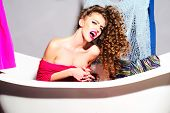stock photo of undressing  - Cute sexy young fashionable undressed woman with curly hair sitting in white bathtub with opened mouth on colorful clothes pink and blue colorss and grey wall background horizontal picture - JPG