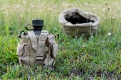 stock photo of canteen  - Army water canteen wiht  desert cover on green grass and blurred military helmet background - JPG