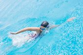 stock photo of crawl  - Young girl in goggles and cap swimming front crawl stroke style in the blue water pool - JPG
