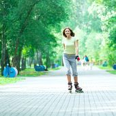 foto of roller-skating  - Roller skating sporty girl in park rollerblading on inline skates - JPG