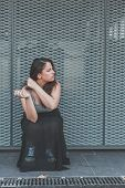 foto of curvy  - Beautiful young curvy girl in tank top smoking a cigarette in an urban context - JPG
