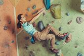 foto of climbing wall  - Climber sporty girl climbing on practice wall indoor - JPG