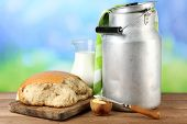 image of milk products  - Retro can for milk with fresh bread and jug of milk on wooden table - JPG