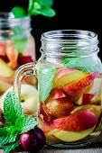 foto of infusion  - Jar delicious refreshing drink of peach fruits and plum with mint on wooden infused water  - JPG
