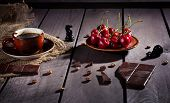stock photo of black-cherry  - Coffee cup dark chocolate and cherries on the wooden table with black chess figure nearby - JPG