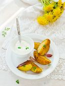 picture of baked potato  - Segments of baked potato and sauce on a white plate - JPG