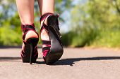 stock photo of ankle shoes  - Beautiful female legs in pink shoes are on the road - JPG