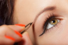 image of eyebrows  - Closeup part of face woman plucking eyebrows depilating with tweezers - JPG