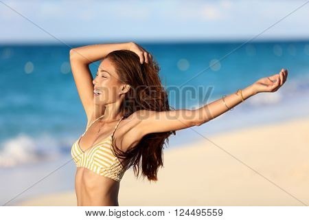Carefree freedom joy bikini woman happy on beach feeling free with arms up at sunset on ocean backgr