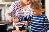 picture of finger-licking  - Family cooking in their kitchen  - JPG