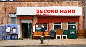 picture of thrift store  - View of thrift storefront with various items displayed on sidewalk - JPG