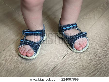e23af18e064 Shod legs of the baby. Children s sandals on their feet. Toddler ...