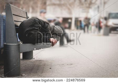 poster of Poor homeless man or refugee sleeping on the wooden bench on the urban street in the city, social documentary concept, selective focus