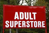 stock photo of porno  - A large red and white sign advertising an Adult Superstore - JPG