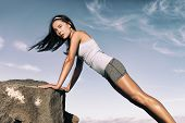 Strength training fitness woman working out core with angled push up exercise on rock. Asian athlete poster