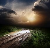 stock photo of ooze  - Muddy wet countryside road and dark storm clouds - JPG