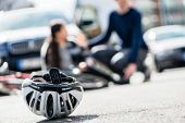 Close-up of a bicycling helmet fallen down on the ground after accidental collision between bicycle  poster