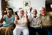 Group of cheerful senior friends sitting and watching TV together poster