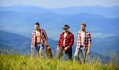 Tourists Hiking Concept. Enjoying Freedom Together. Group Of Young People In Checkered Shirts Walkin poster